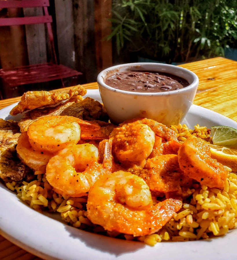 Shrimp is seen with a spicy red sauce atop rice and served with beans on the side in a bowl