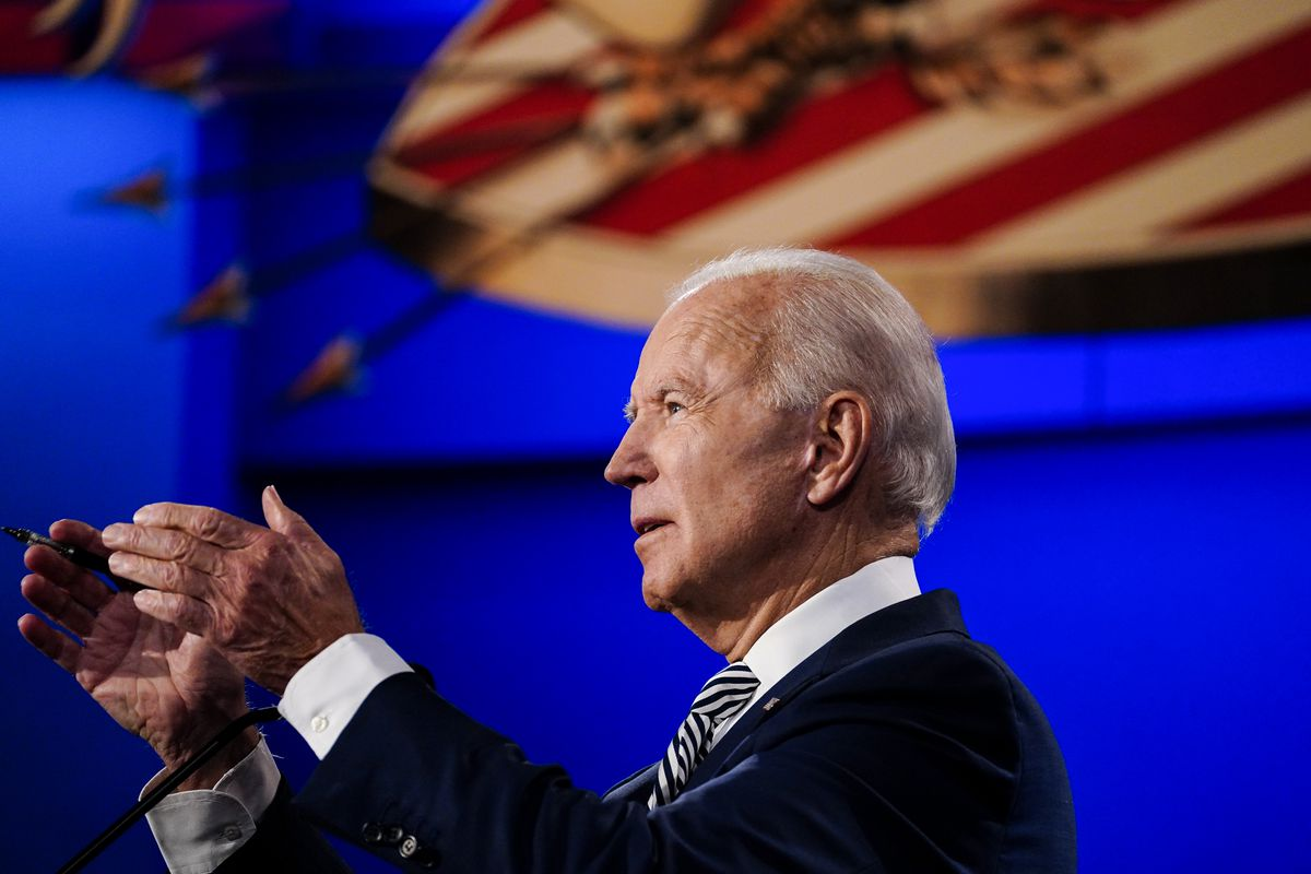 Joe Biden, in a dark suit and tie with black and white stripes, gestures with both hands above a microphone he's speaking into. Behind him is the image of a red and white striped shield, with four arrows across it.