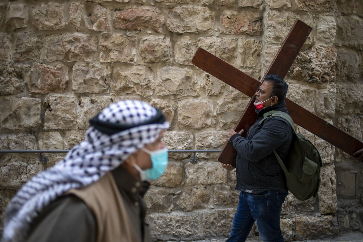 A Christian carries a cross as he walks along the Via Dolorosa towards the Church of the Holy Sepulchre, traditionally believed by many to be the site of the crucifixion of Jesus Christ, during the Good Friday procession in Jerusalem's old city, Friday, April 2, 2021.