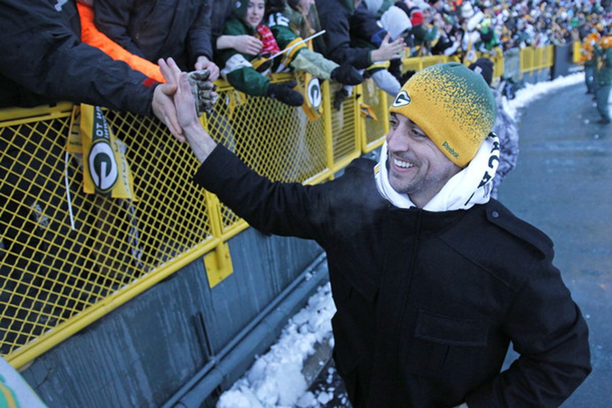 GREEN BAY WI - FEBRUARY 08: Green Bay Packers quarterback Aaron Rodgers slaps the hands of fans as he leaves the field after the Packers victory ceremony at Lambeau Field on February 8 2011 in Green Bay Wisconsin.  (Photo by Matt Ludtke/Getty Images)