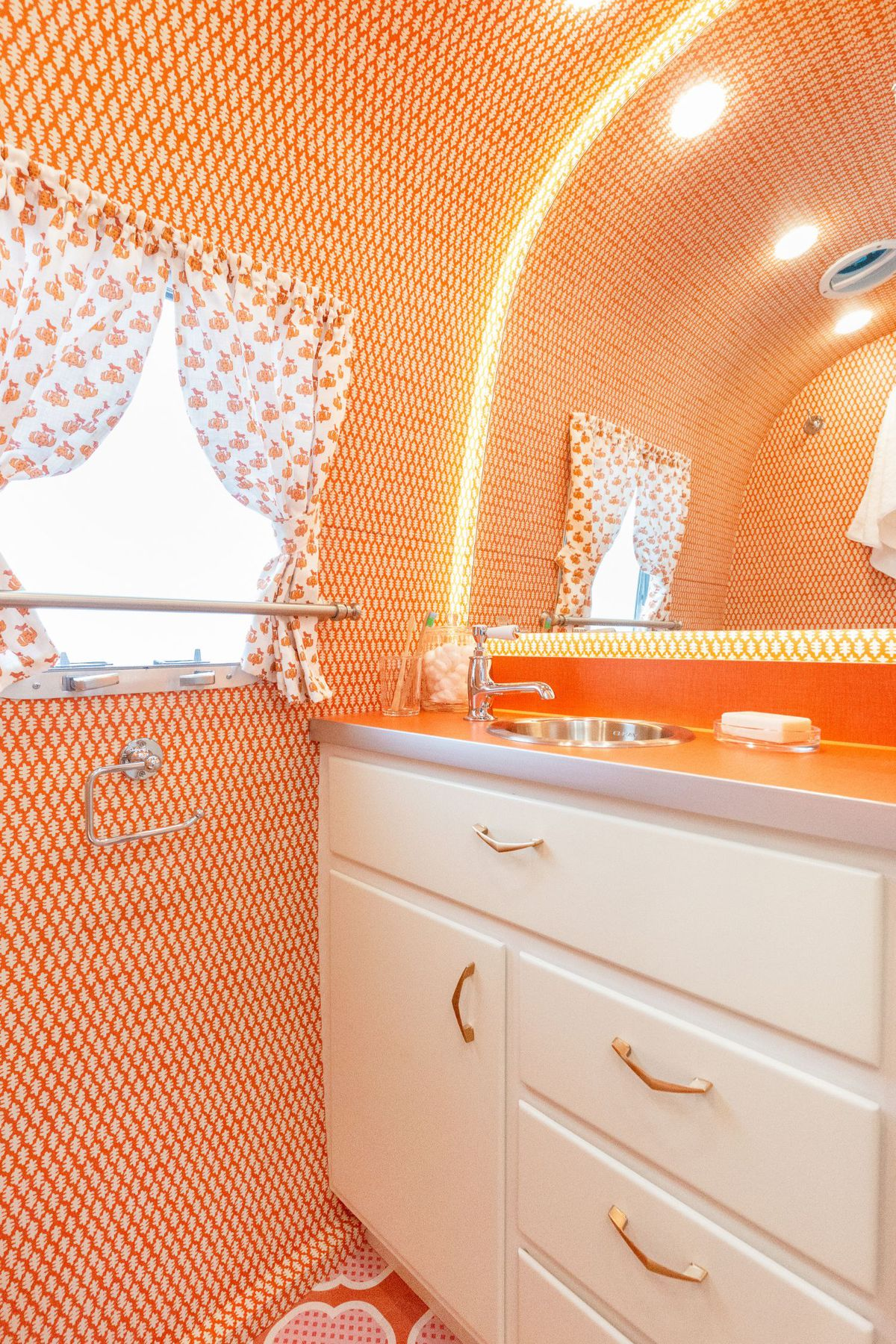 The bathroom features small coral tiles, a white cabinet, and bright orange countertops.