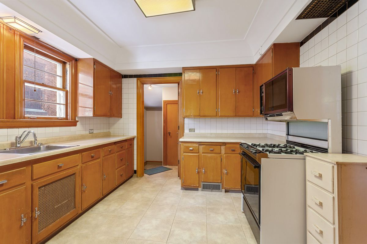 A kitchen with original cabinets. There is beige tiling and white backspash tile.
