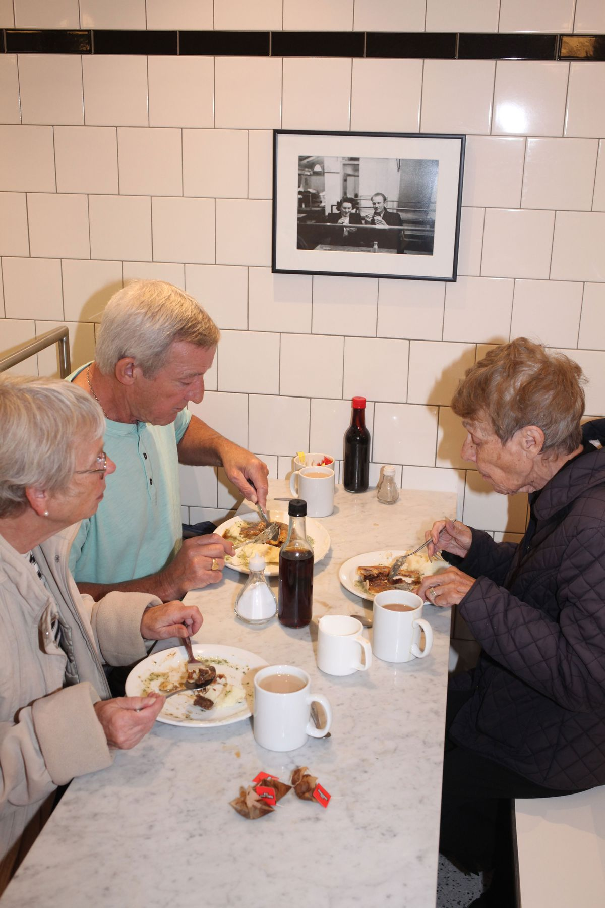 Customers eating pie and mash at G.Kelly on Roman Road, east London