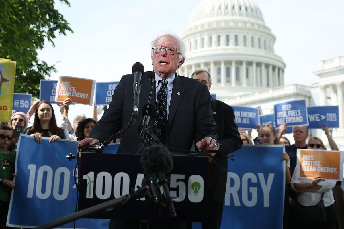 An older man with white hair speaks before the U.S. Capitol with a rally taking place behind him.