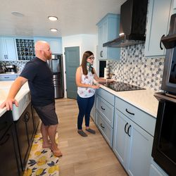 Trevor Andersen watches as his wife, Brooke, points out items that make it easier for her to work in the kitchen of their Provo home on Wednesday, July 7, 2021. Brooke Andersen's spinal fusion surgery was delayed because of COVID-19 closures, but she finally made it to Spain during its brief opening window to have it. Now she can walk again, but she's still facing a lifetime of deterioration from her condition.