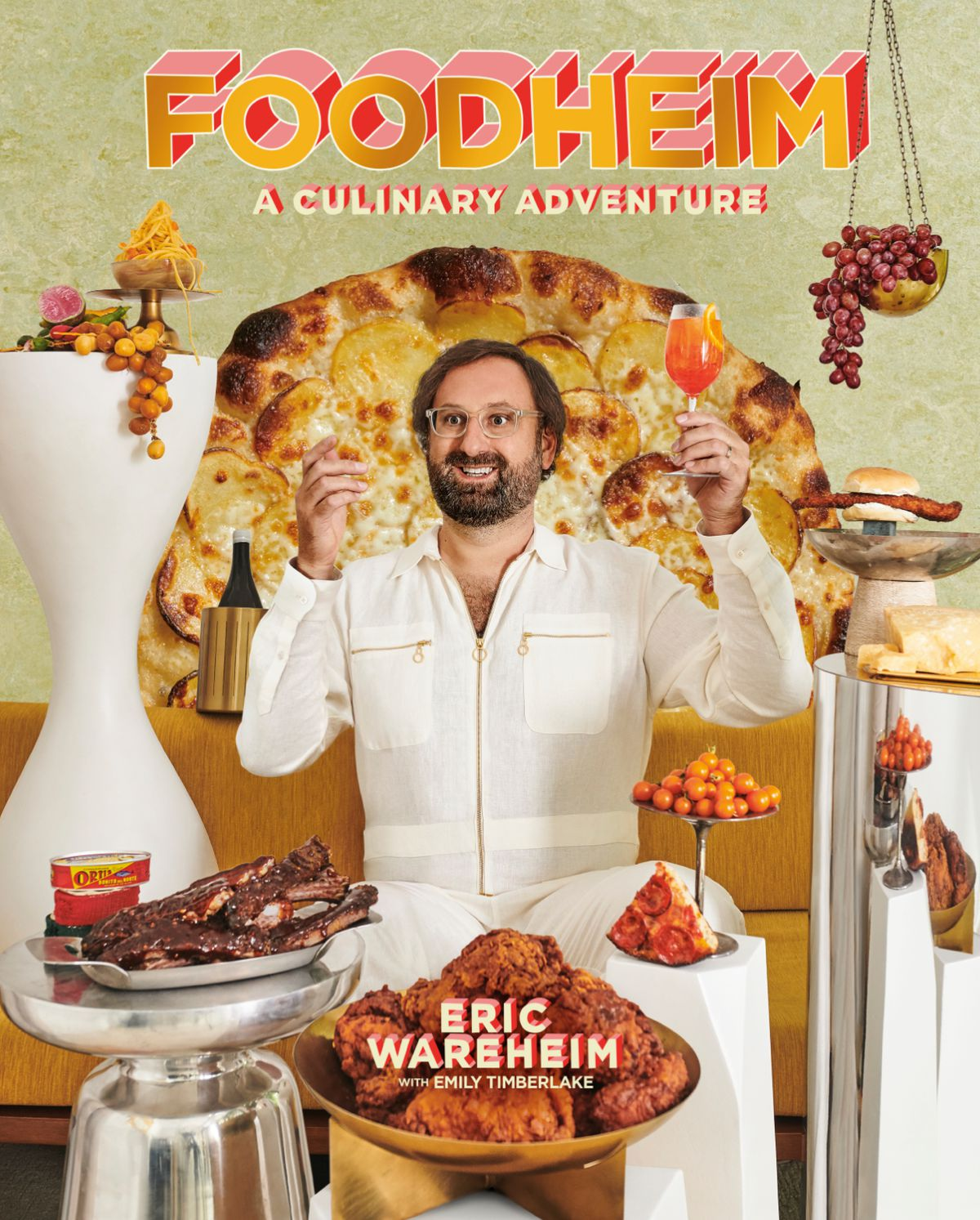 A man dressed in white, Eric Wareheim, raises a glass of aperol spritz while surrounded by opulent foods