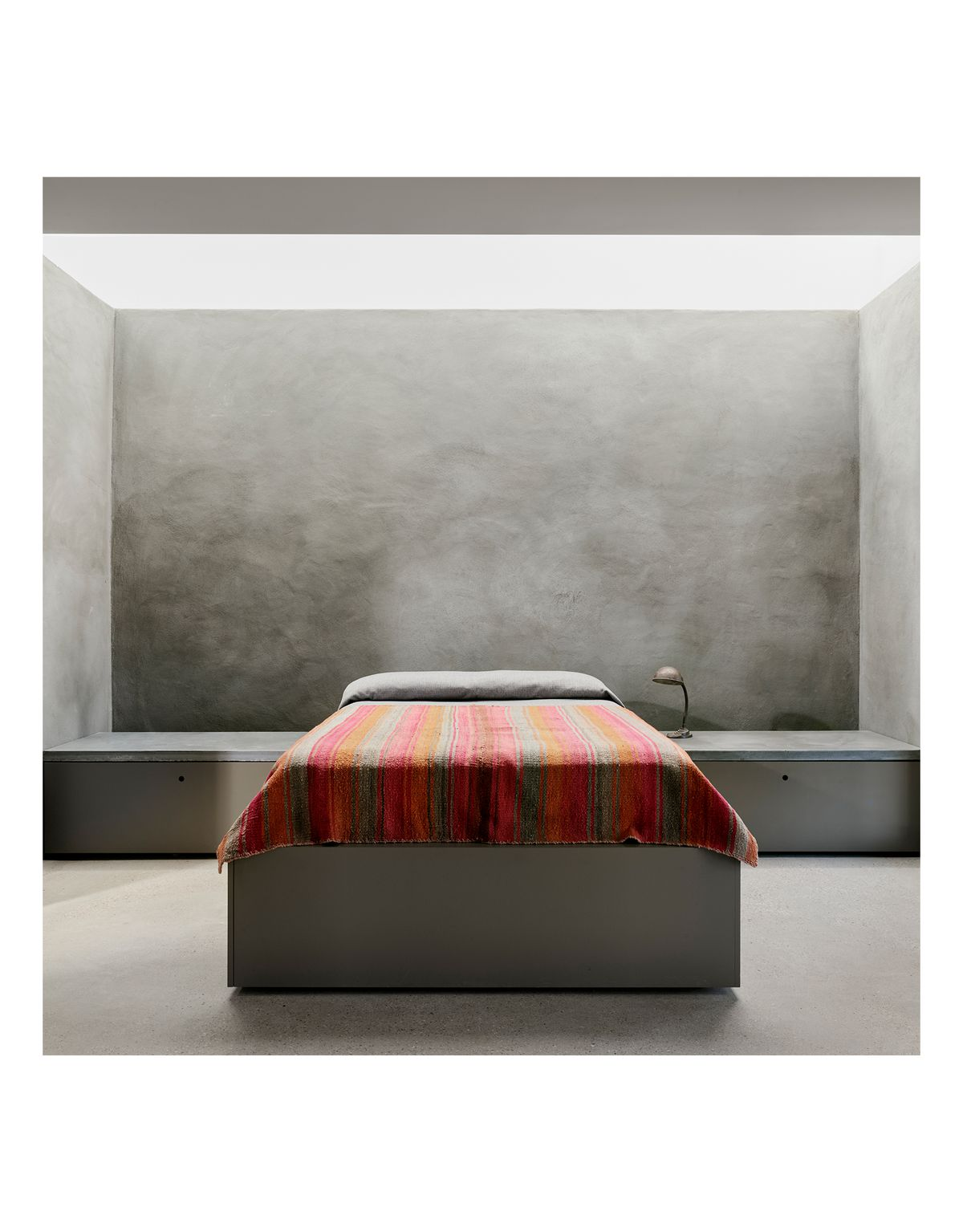 A red and brown blanket on the bed makes a bright spot of color in the neutral environment.