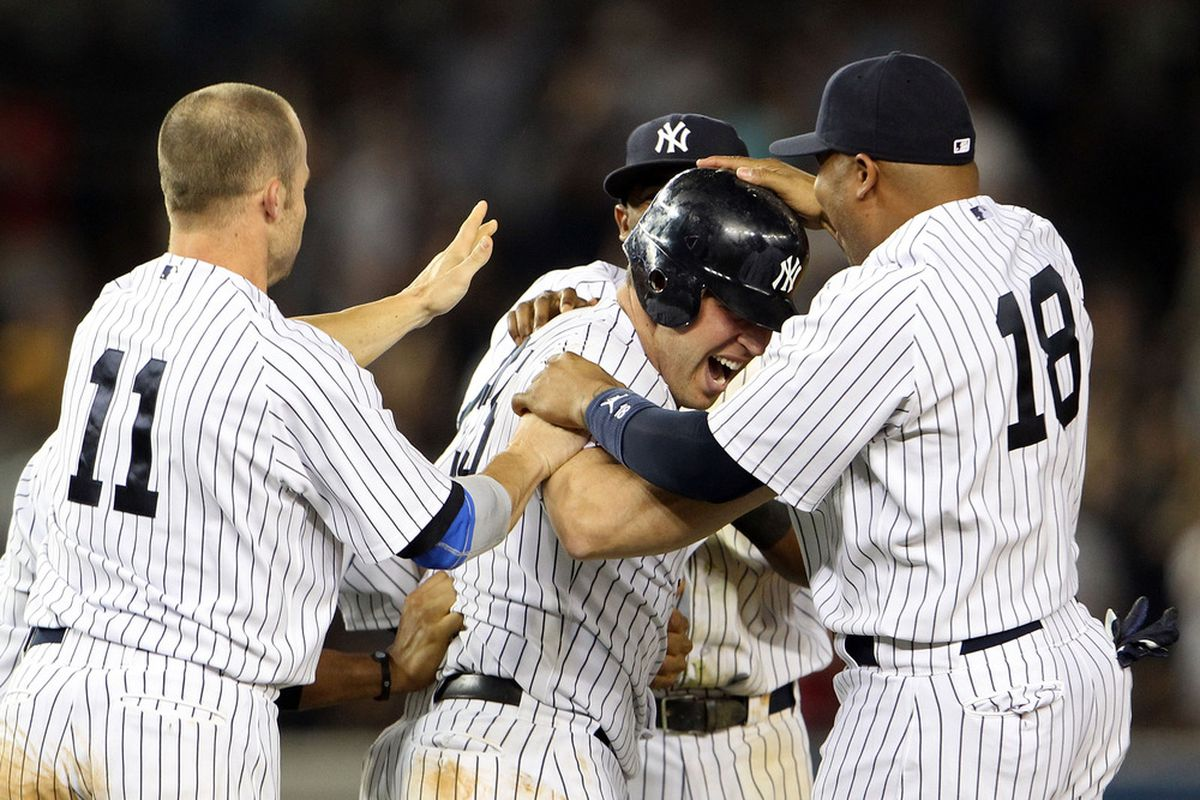 Mark Teixeira (25) of the New York Yankees celebrates with Brett Gardner (11) and Andruw Jones(18) after hitting a game winning RBI in the ninth inning against the Toronto Blue Jays at Yankee Stadium on May 24.  (Photo by Michael Heiman/Getty Images)