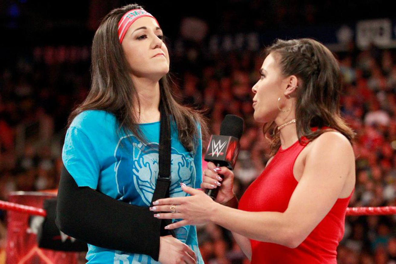 Bayley in the ring with an arm sling w/ ring announcer