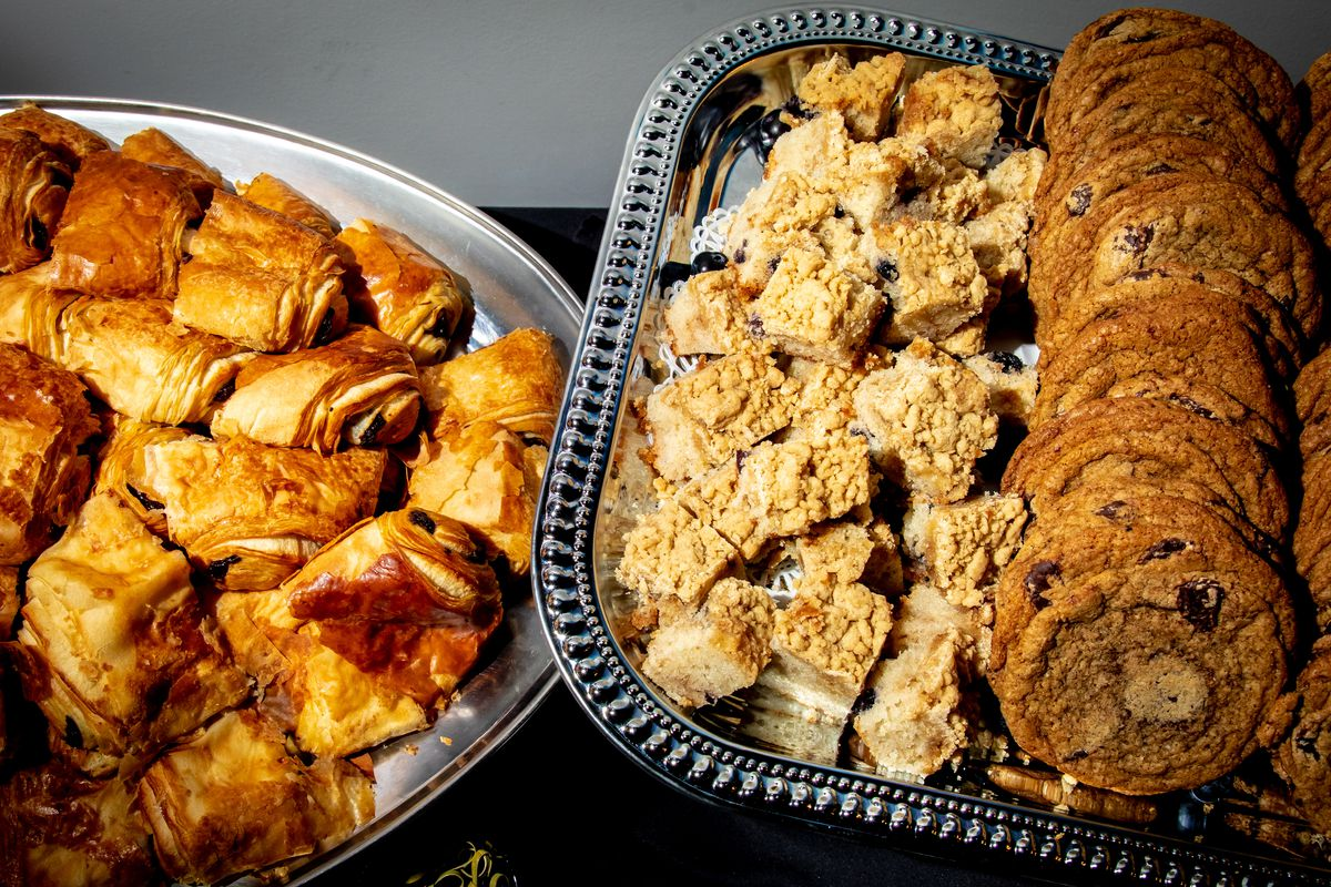 A platter of rugelach next to a platter of cookies.