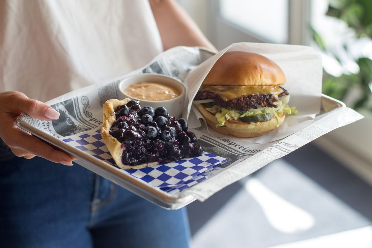 burger and blueberry pie on a tray and with blue and white checkers held by a woman