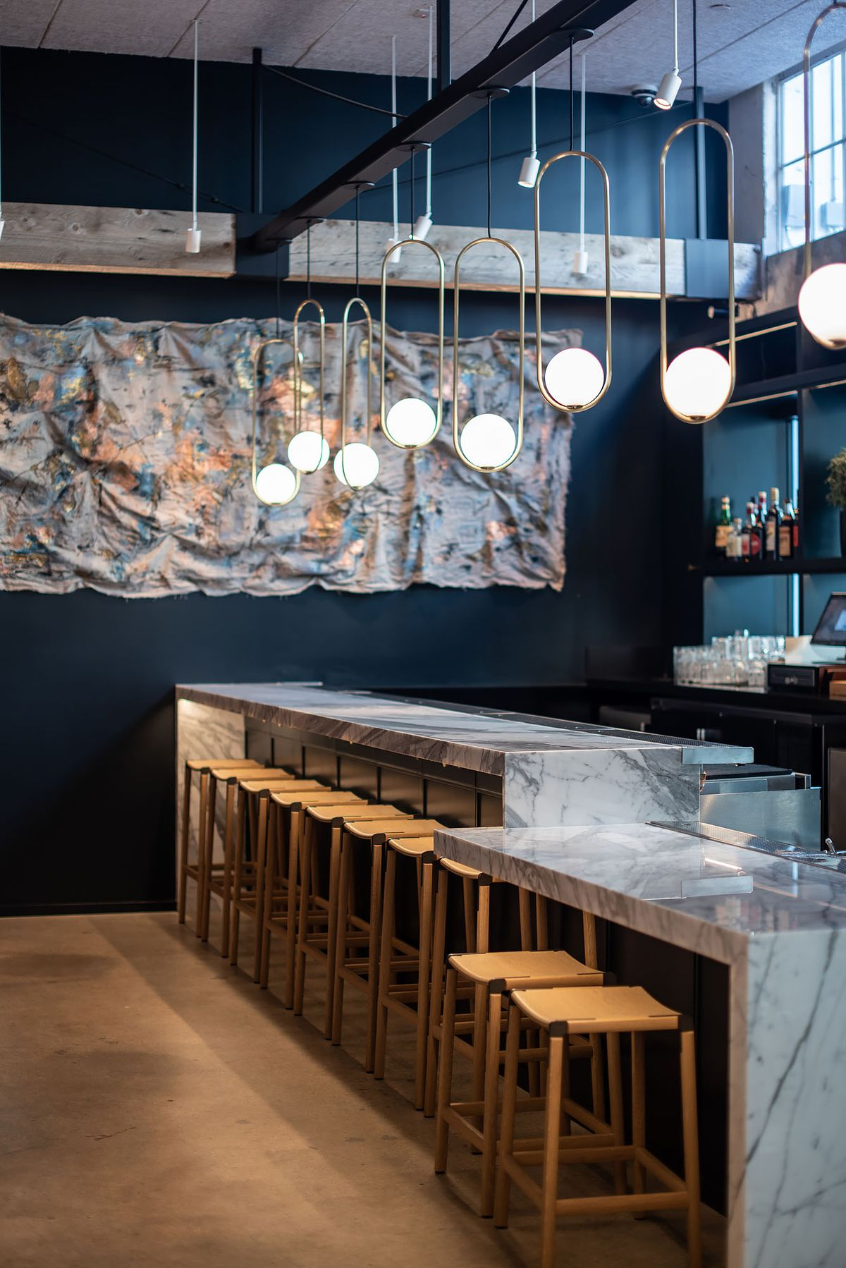 A short marble bar with wooden stools at a hip new restaurant.