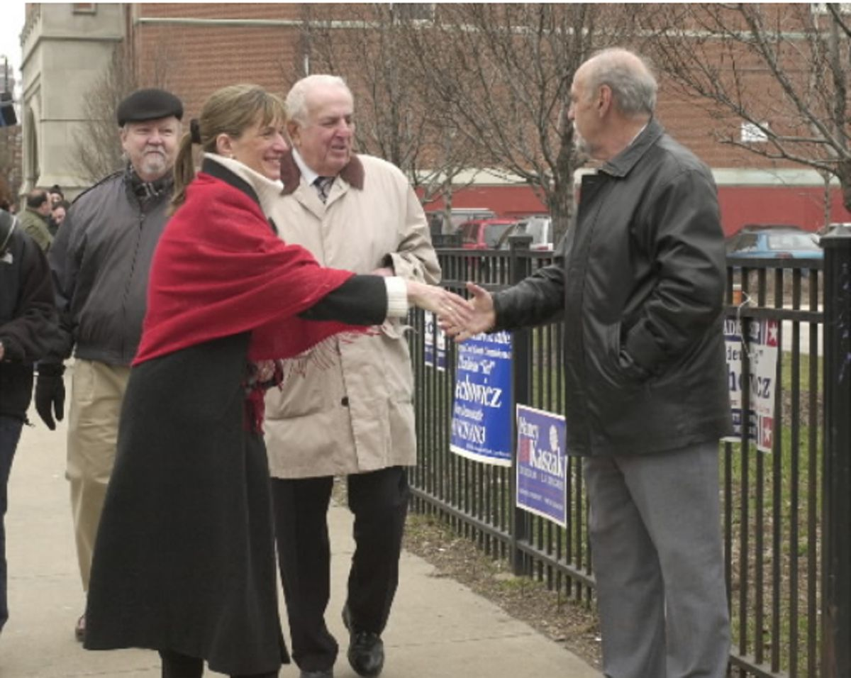 Dr. Benjamin Emanuel shakes hands with congressional candidate Nancy Kaszak after she voted in 2002. Behind Kaszak, who unsuccessfully ran against Rahm Emanuel, are her husband Tom Heaney and Abner Mikva, the former congressman and judge.