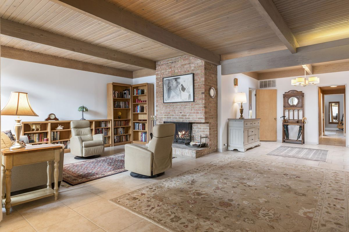 A foyer and living room with a wood ceiling and a brick-lined fireplace.