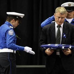 Rand Beers, right, acting Secretary of the U.S. Department of Homeland Security collects the memorial flag to present to Ana Hernandez, wife of slain TSA Officer Gerardo Hernandez  after he spoke during the memorial service at the Los Angeles Sports Arena,  Tuesday, Nov. 12, 2013 in Los Angeles. At a memorial service filled with tears, prayers and songs, Gerardo Hernandez, the Transportation Security Administration officer who was killed by a gunman at Los Angeles International Airport was remembered Tuesday as a devoted public servant who greeted every traveler with a grin and never passed up an opportunity to talk about his children.