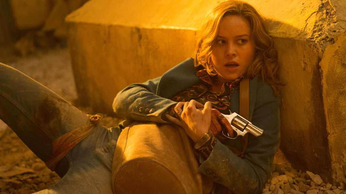 Brie Larson holds her pistol behind a rock brick in Free Fire