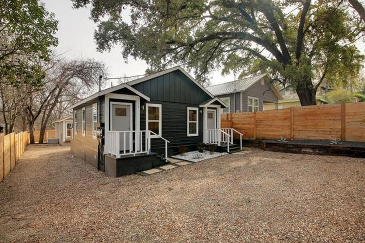 Small wooden duplex painted dark gray, one story