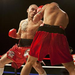 """Chris """"KidKayo"""" Fernandez, left, and Allen Litzau trade blows during their boxing match at the South Towne Expo Center. Fernandez won the bout after four rounds, Saturday, Dec. 15, 2012."""