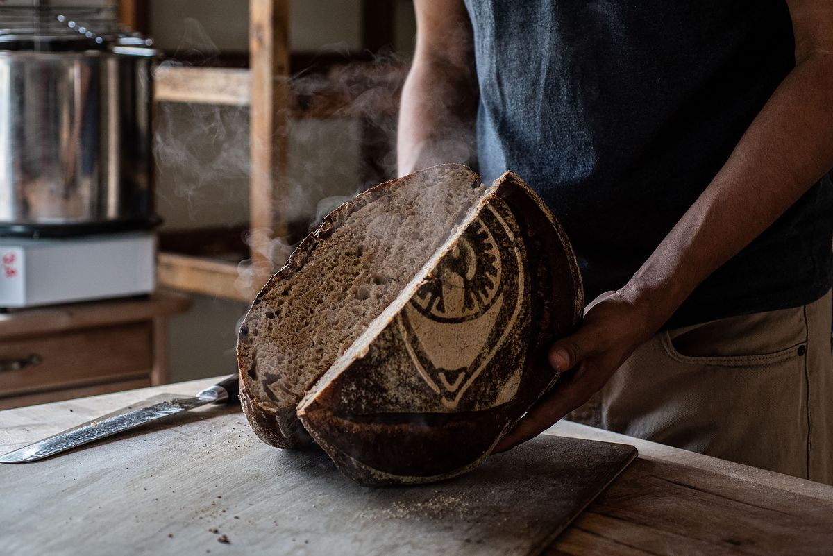 A home baker opens his finished bread as steam escapes.