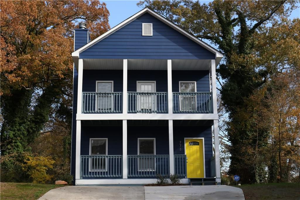 Two-story blue house with white trim and yellow front door.