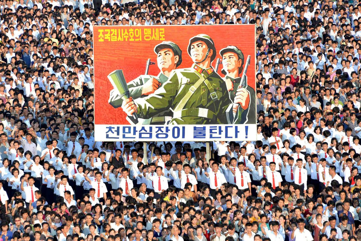 North Korean people wearing white shirts and red ties march and hold a huge banner depicting soldiers with guns.