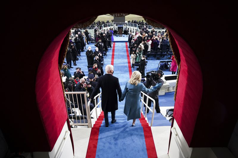 Joe and Jill Biden enter the inauguration stage at the Capitol.