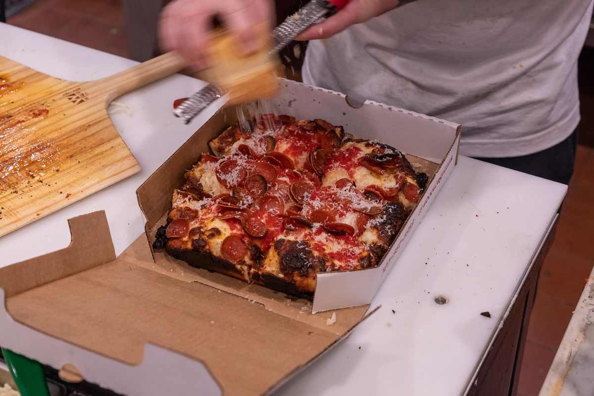 A worker pours on shaved cheese atop a just finished pizza.