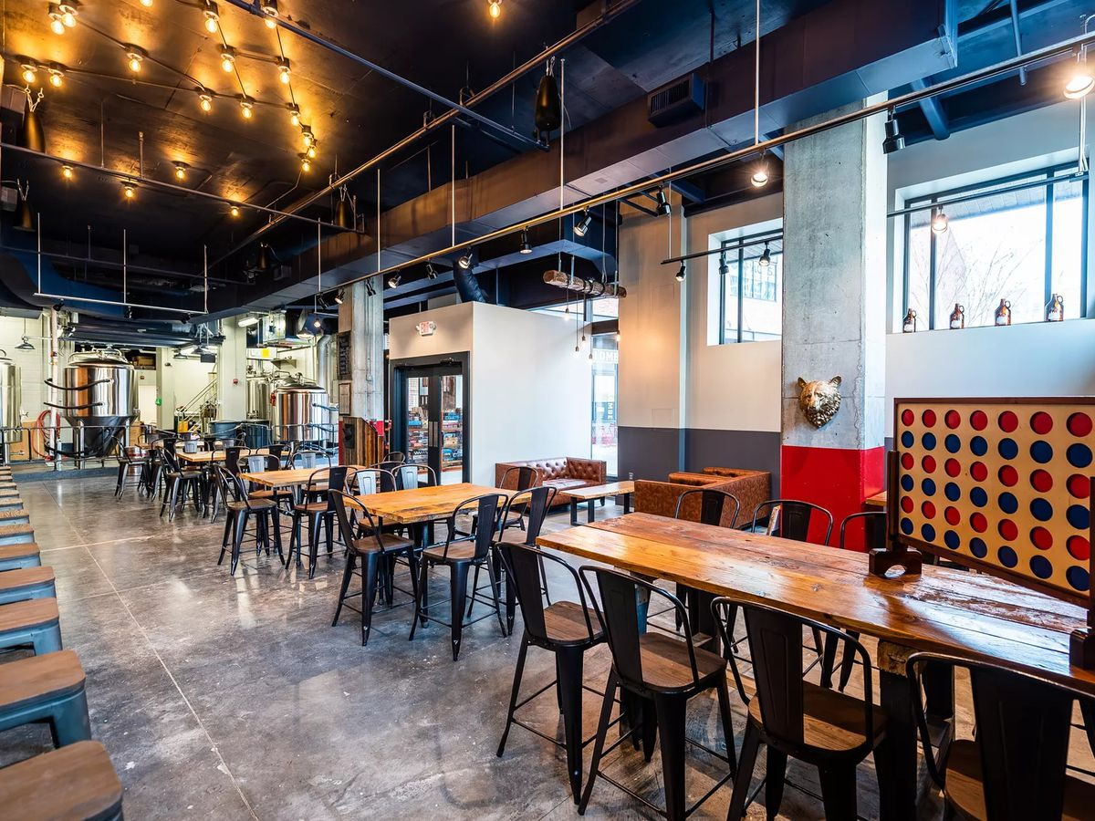 Tables, chairs, and a set of Connect 4 inside Red Bear Brewing Co