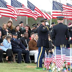 Dennis Weichel, seated, far left, father of Rhode Island National Guardsman Sgt. Dennis Weichel Jr., watches as the flag covering his son's casket is folded during funeral services at the state Veterans Cemetery in Exeter, R.I., Monday, April 2, 2012.  Weichel Jr., was struck and killed by an armored vehicle March 22 in Afghanistan while saving an Afghan boy. Weichel was posthumously awarded the Bronze Star and NATO Service Medal Afghanistan Campaign Ribbon RI Star.