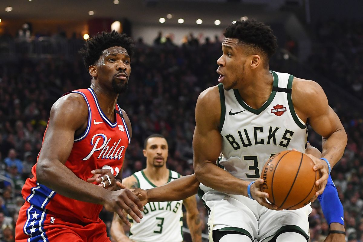 Giannis Antetokounmpo of the Milwaukee Bucks is defended by Joel Embiid of the Philadelphia 76ers during a game at Fiserv Forum on February 22, 2020 in Milwaukee, Wisconsin.