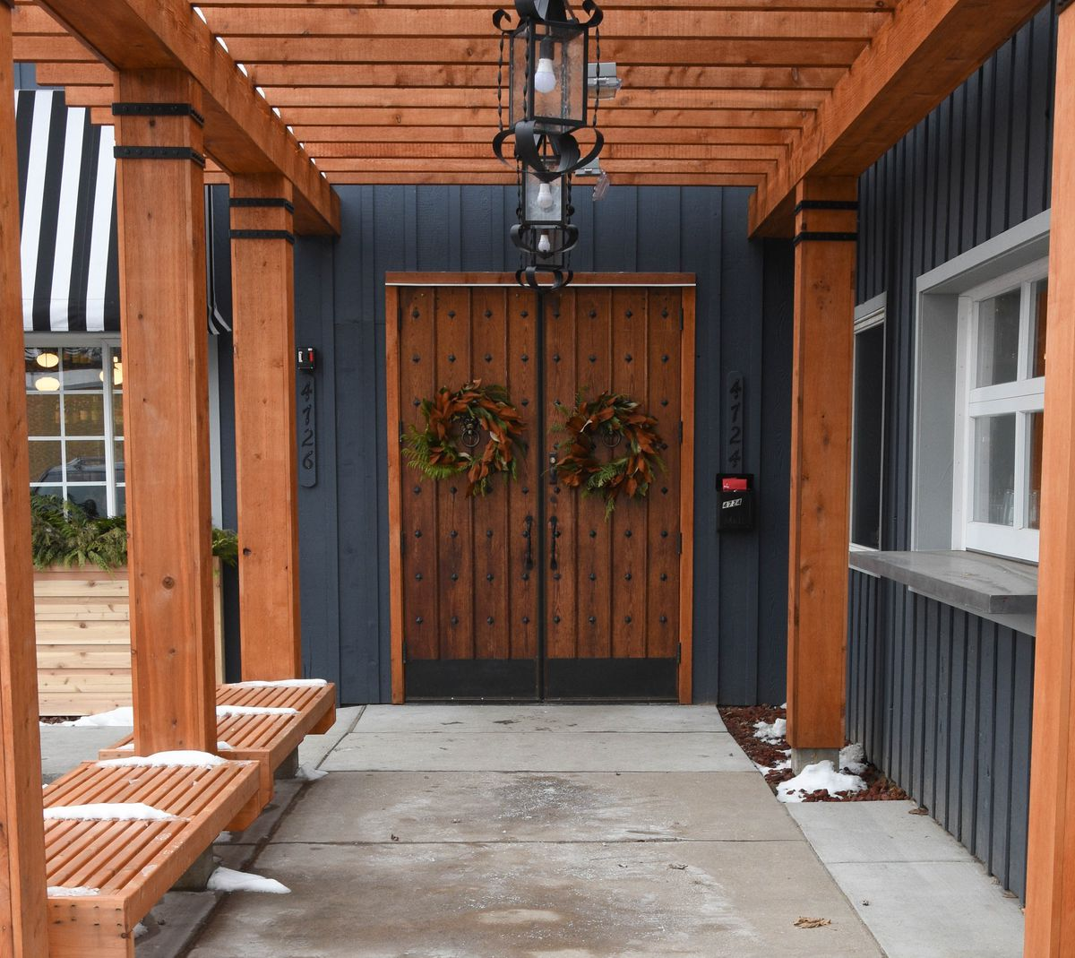 The double wood doors with a Christmas wreath at Italian Eatery