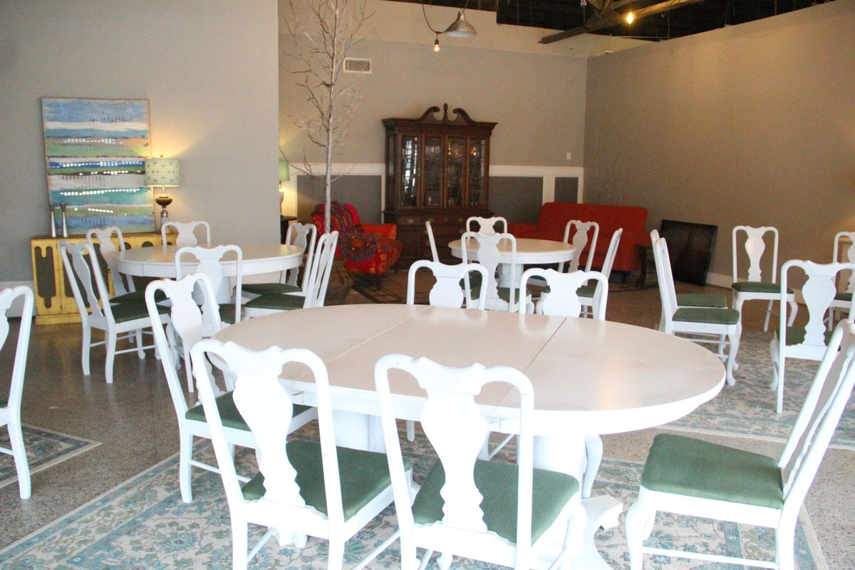 A large gray room with white chairs and a few carpets.