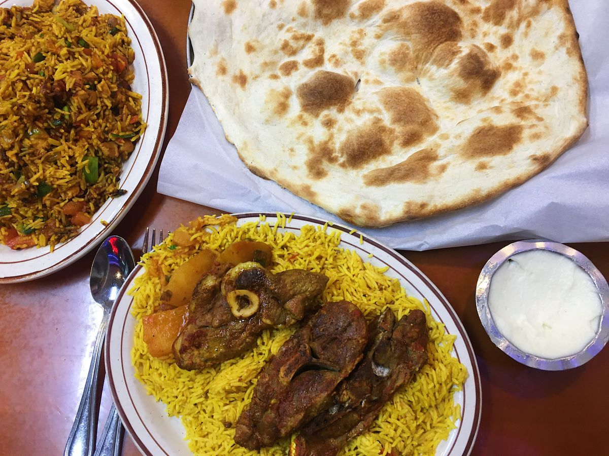 Lamb on saffron rice, a plate of rice mixed with chicken and vegetables, and a large piece of Yemeni flatbread next to a silver dish of garlic paste.