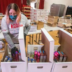 A volunteer helps pack food for people in need at the local Salvation Army in Salt Lake City on Tuesday, Dec. 15, 2020.