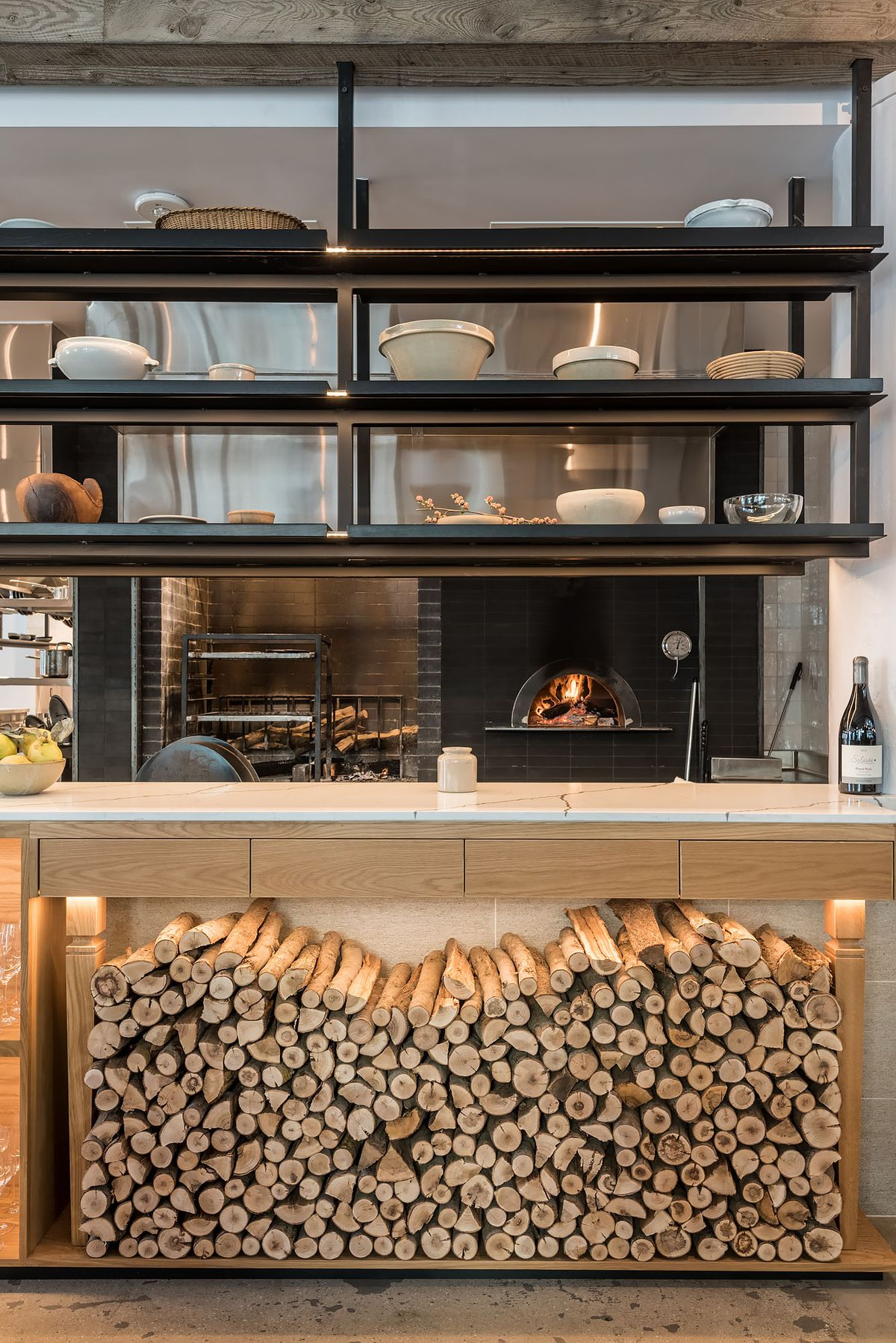 A trim stack of wood next to an open wood-fired oven at a new restaurant.