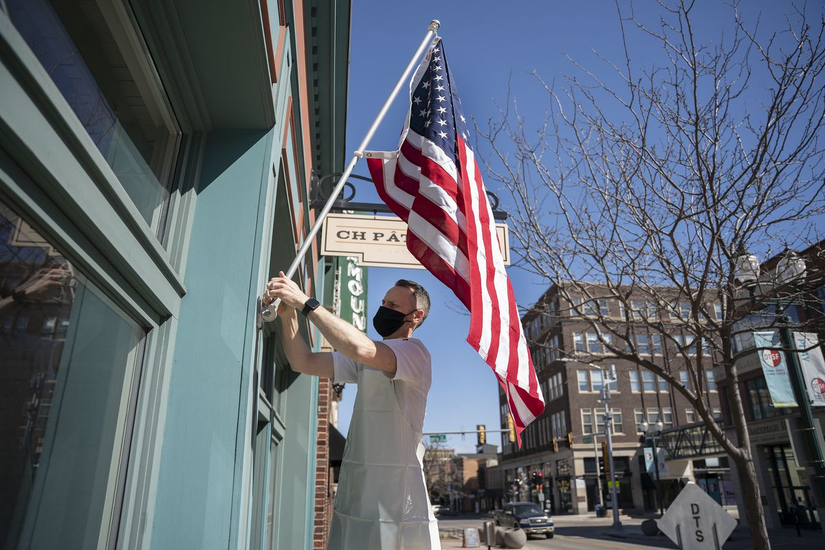 Chef Chris Hanmer sets up the flag in front of his business in Sioux Falls, South Dakota, on April 21, 2020.