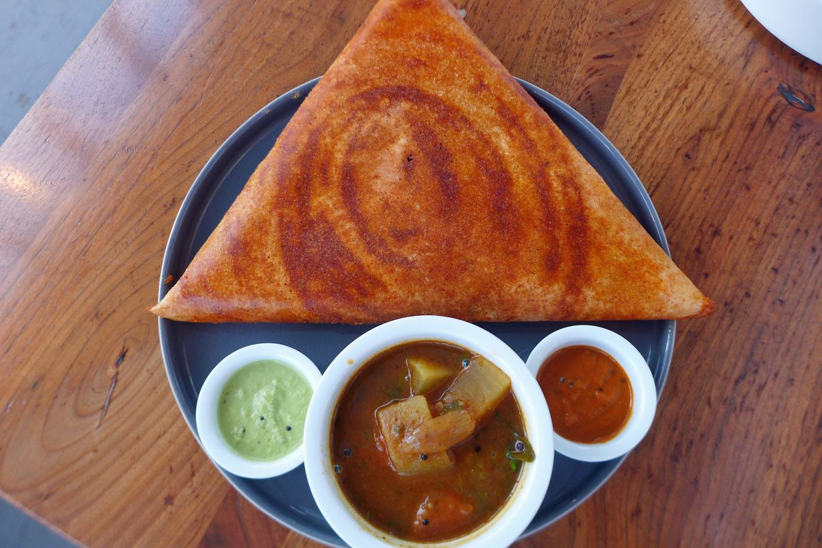 A perfect equilateral triangle of a dosa, with three sauces underneath in tiny bowls.