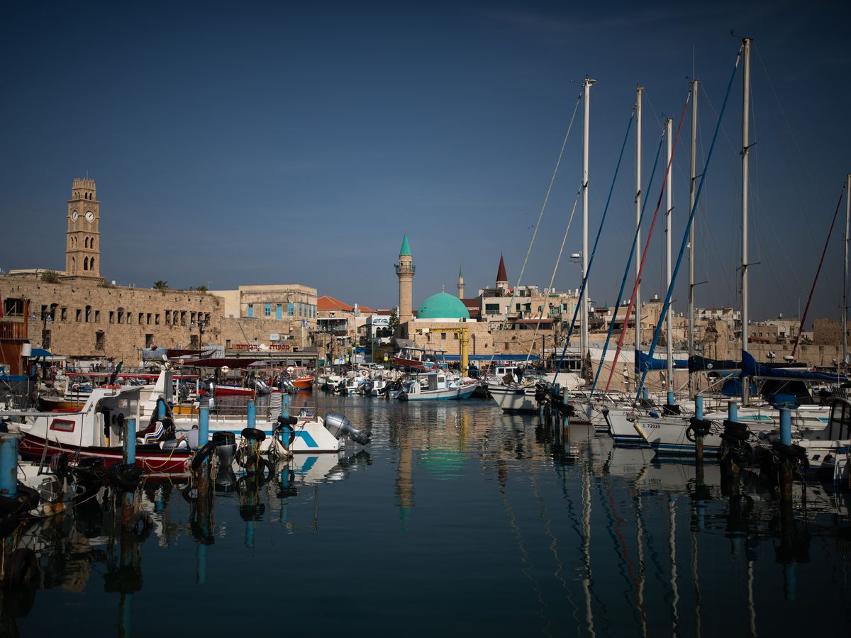 Boats sit in a harbor with a green dome in the distance