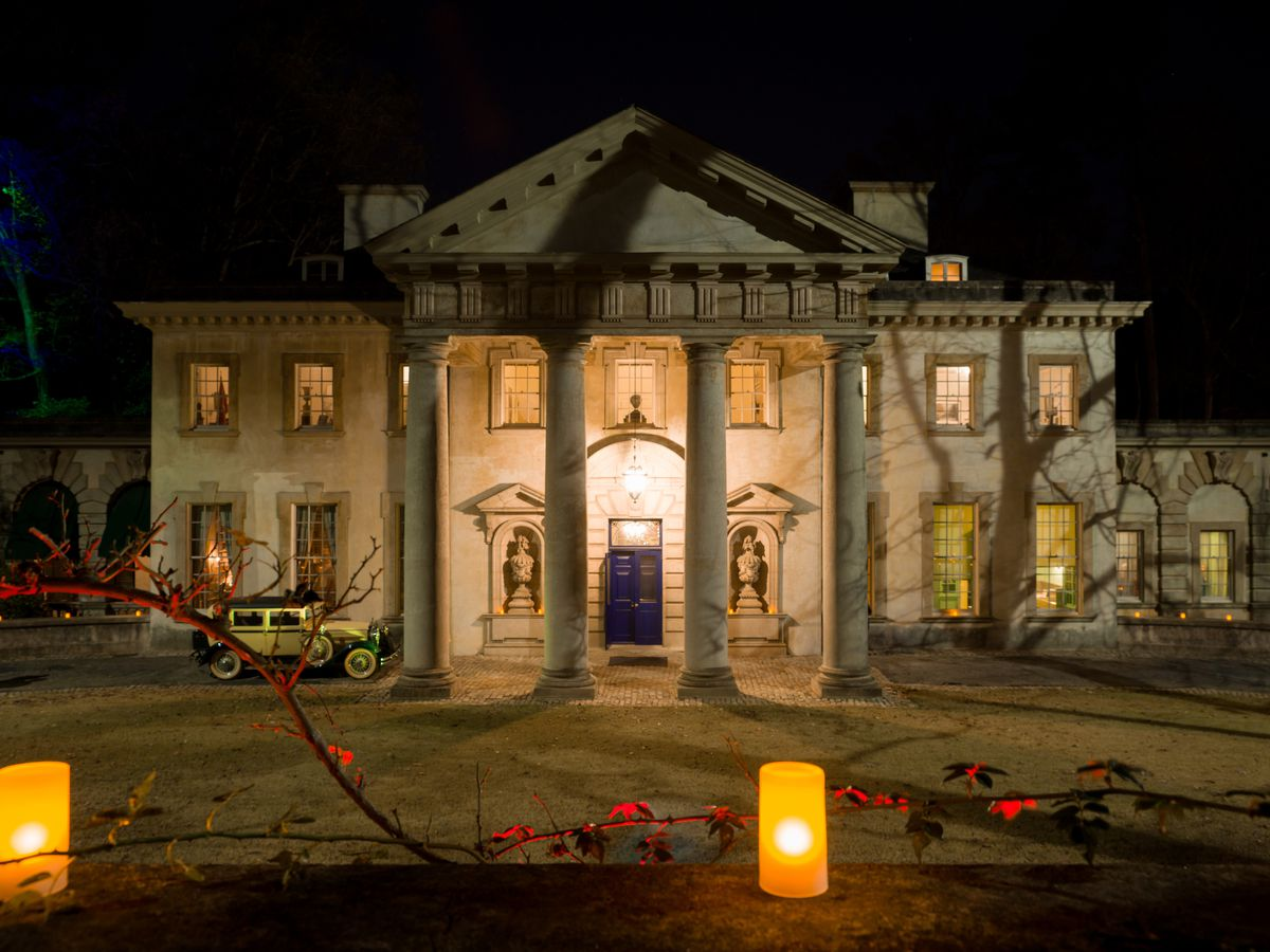 A large mansion at night with columns and many windows. In front of the mansion are candles and string lights.