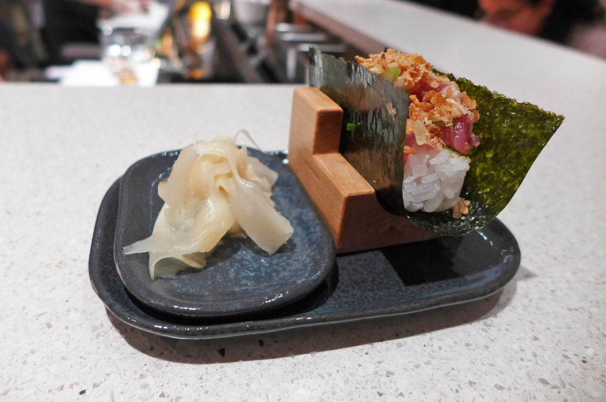 A sheet of nori contains rice, tuna, and crunchy shallots on top, with a plate of pickled ginger sliced thin on the side...