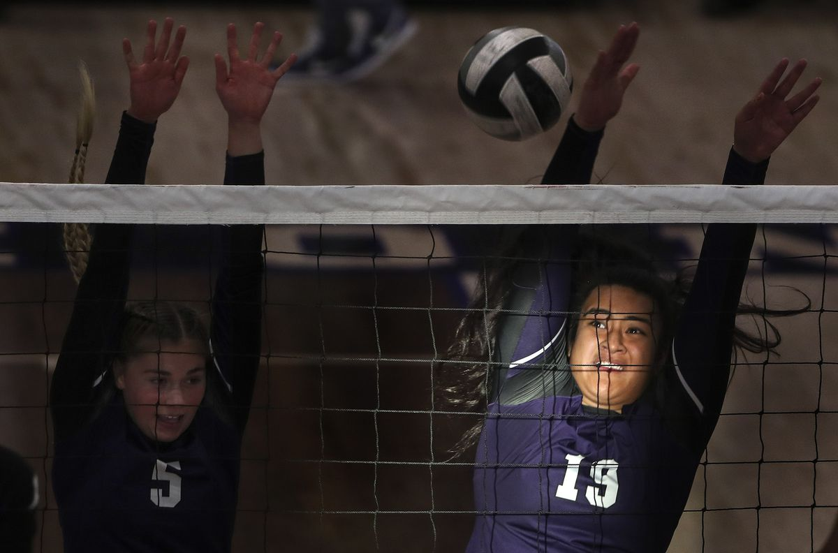 Light from a window shines on Lehi's Divine Faleao as she tries to block a Pleasant Grove shot with teammate Haylee Holker during volleyball match at Lehi High School on Tuesday, Aug. 18, 2020.