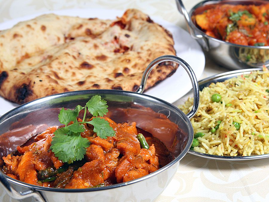 A closeup view of a dish stewed in a red sauce, with sides of naan and rice in the background.