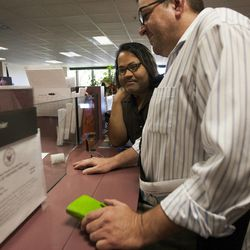 Ariel Ulloa Gonzalez, left, and Gregory Enke pay for their marriage certificate at the Salt Lake County Clerk's Office in Salt Lake City, Monday, Oct. 6, 2014.