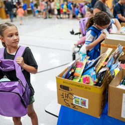 Scarlet Blanton, 8, looks over boxes of free school supplies as she fills a backpack during Operation Homefront's annual Back-to-School Brigade event at Hill Field Elementary in Clearfield on Tuesday, Aug. 13, 2019.