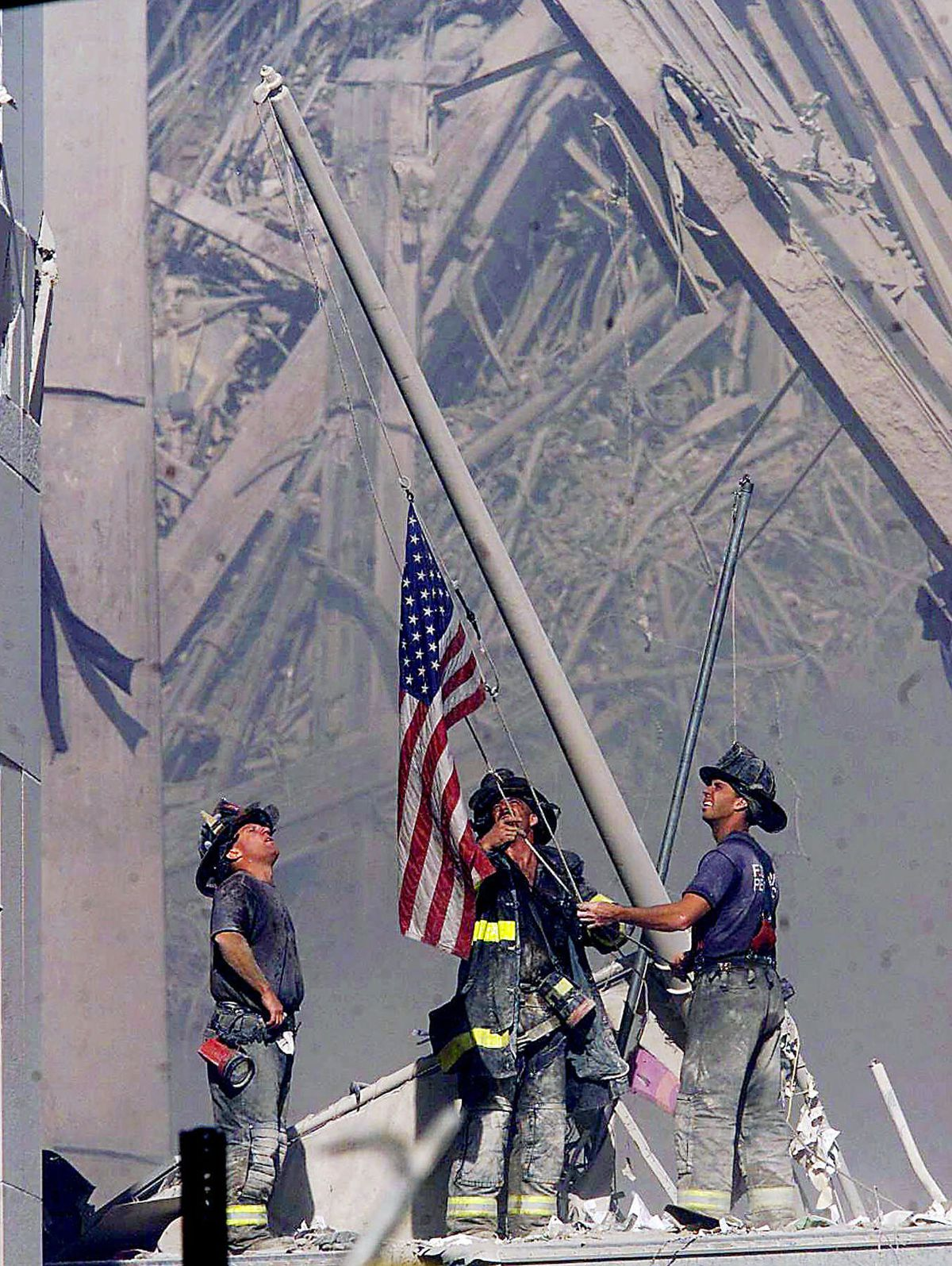 Brooklyn firefighters George Johnson, left, of ladder 157, Dan McWilliams, center, of ladder 157, and Billy Eisengrein, right, of Rescue 2, raise a flag at the World Trade Center in New York in this Sept. 11, 2001 file photo.
