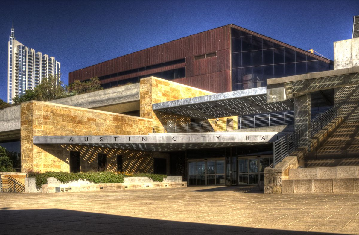 The exterior of Austin City Hall. The facade is mixed materials. There is a metallic sign above the entrance that reads: Austin City Hall.