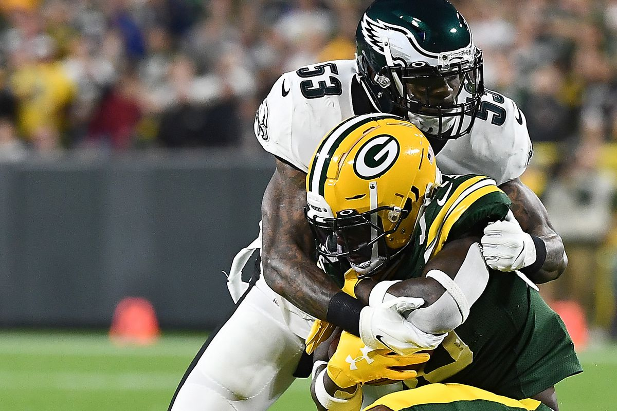 Running back Jamaal Williams of the Green Bay Packers is tackled by Nigel Bradham of the Philadelphia Eagles before a helmet-to-helmet hit in the first quarter of the game at Lambeau Field on September 26, 2019 in Green Bay, Wisconsin.