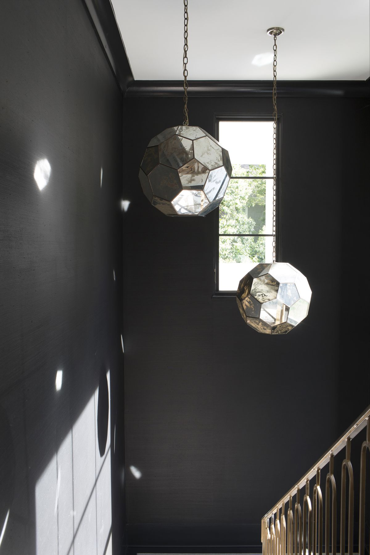 A black-painted stairwell features two geometric, mirrored pendants that hang from the ceiling.