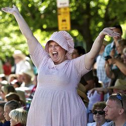 Nancy Bittner of Centerville, Utah waves to the parade participants as she and other spectators watch the floats, horses and celebrities participate in the Days of '47 Parade in Salt Lake City Saturday.