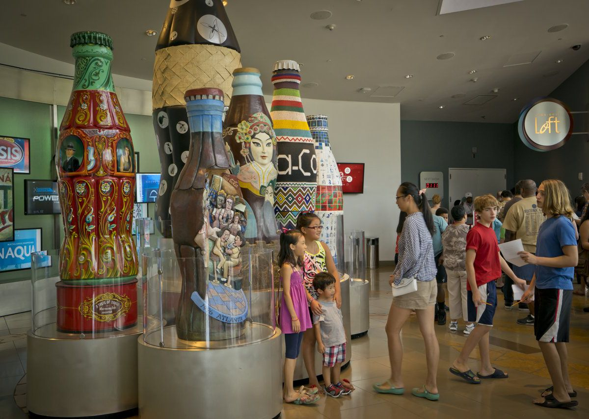 Family posing in front of very large Coca-Cola bottles.